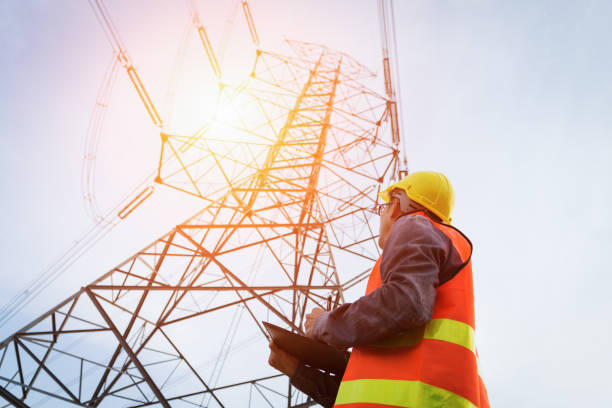 Engineering working on High-voltage tower, stock photo
