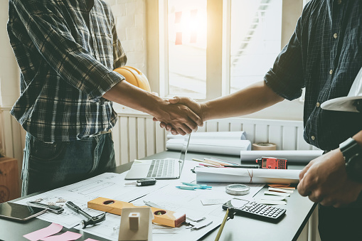 912867216 istock photo Engineers and architects handshake. Agreement and are willing to work together. 1068877076