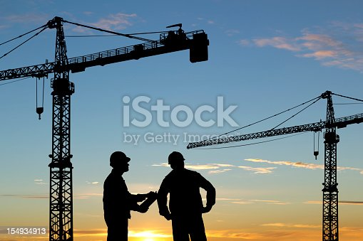 Royalty free image of two construction workers surveying a construction site and cranes.