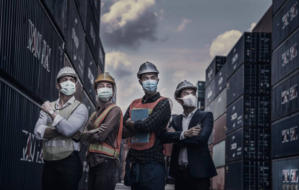 Engineers and Foreman who wear a mask that join forces against the virus, Covid 19 At the container yard stock photo