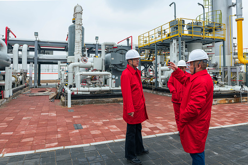 Engineers and staff communicate on site in chemical plant