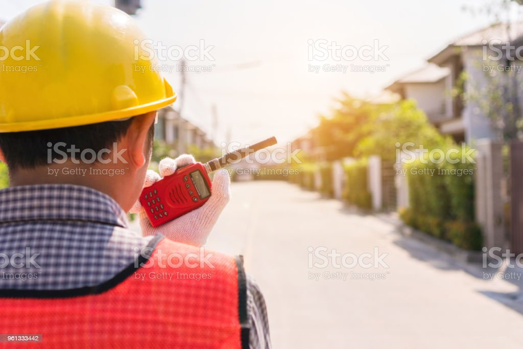 Engineers are using walkie-talkie to explain employees what to do. Copy space. stock photo