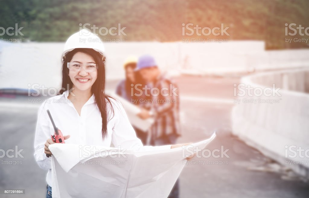 Engineers asia woman holding blueprint with radio for workers security control at power plant energy industry. Engineer Concept stock photo