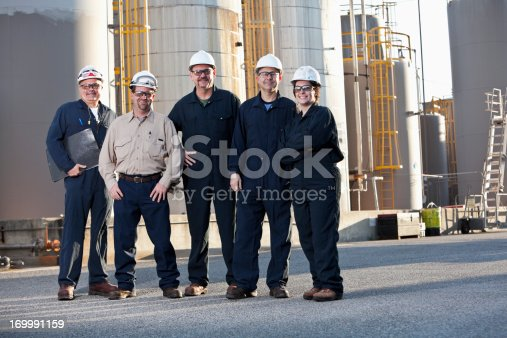 Engineers working at chemical plant standing in front of storage tanks.