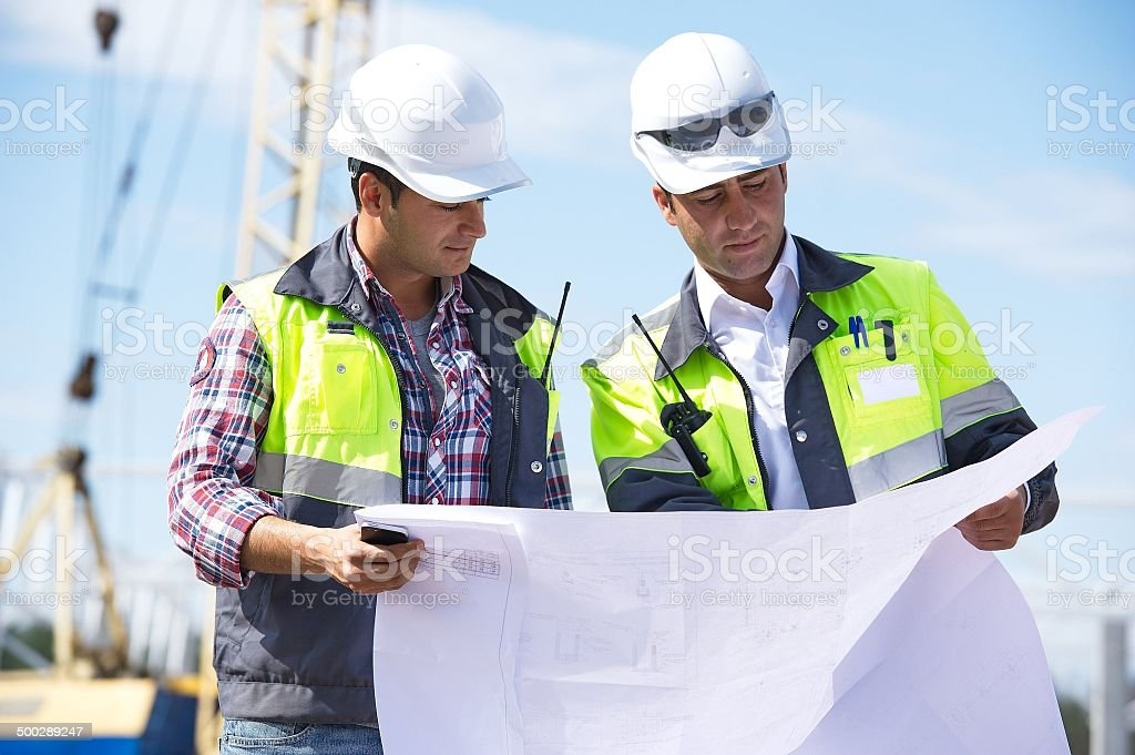Engineers At Construction Site Two engineers at construction site are inspecting works according to design drawings. Adult Stock Photo