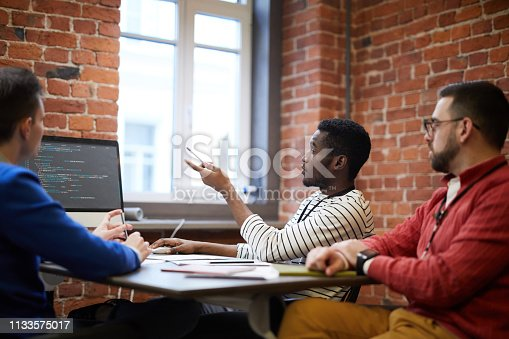 Three young intercultural it-engineers sitting by table in front of computer monitor and discussing new language