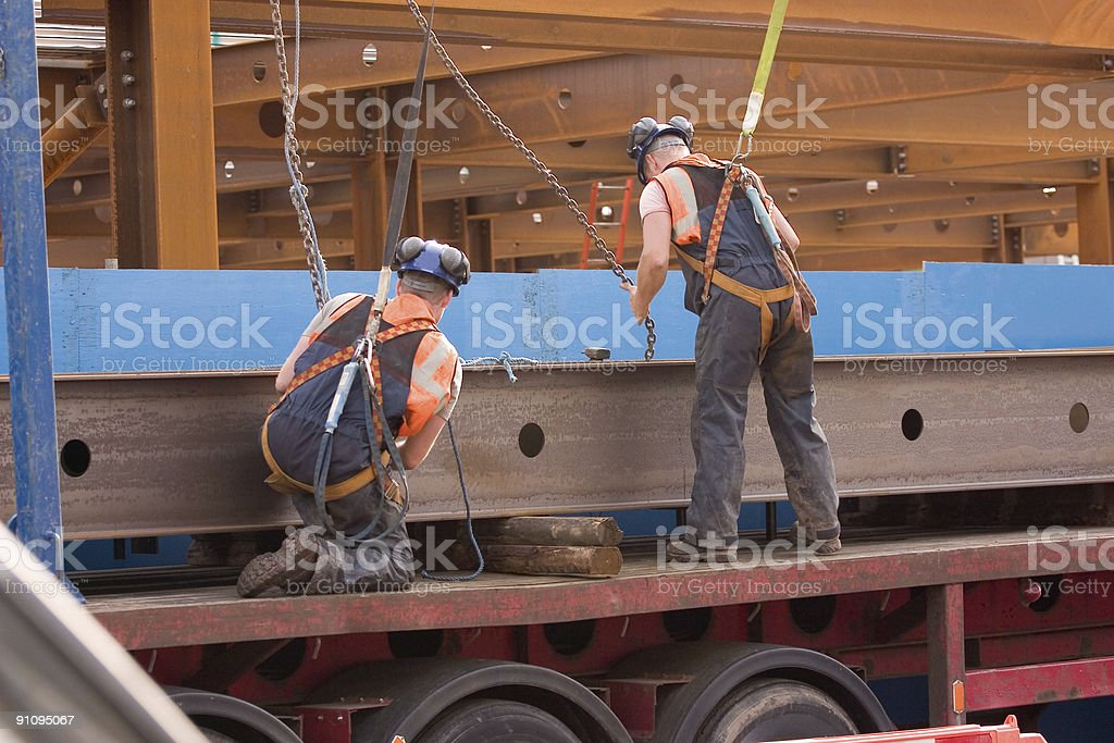 Engineers at work unloading steel girders from a lorry stock photo