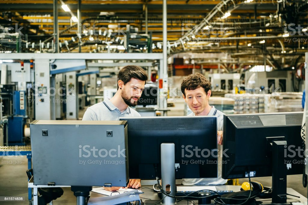Engineers behind several Computer Monitors in a huge factory stock photo