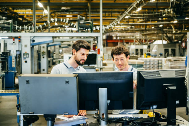 engineers behind several computer monitors in a huge factory - automated stock photos and pictures