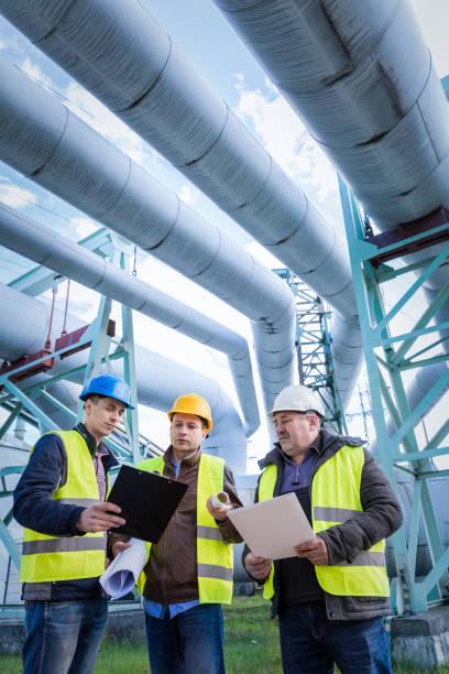 ingenieure, die wartung einer petrochemischen anlage diskutieren - petrochemische fabrik stock-fotos und bilder