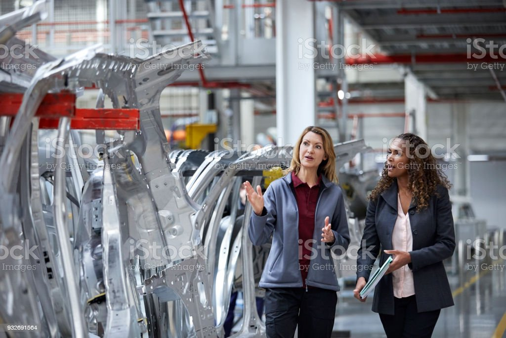 Engineers discussing over car chassis in factory stock photo