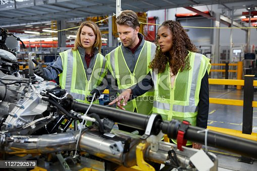 istock Engineers discussing over car machinery in factory 1127292579