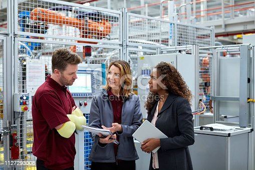 istock Engineers discussing over documents in car plant 1127293008