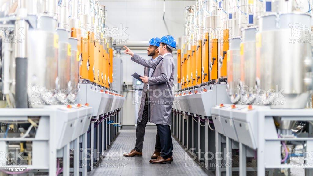 Ingenieure untersuchen eine Maschine in einer Fabrik - Lizenzfrei Afrikanischer Abstammung Stock-Foto