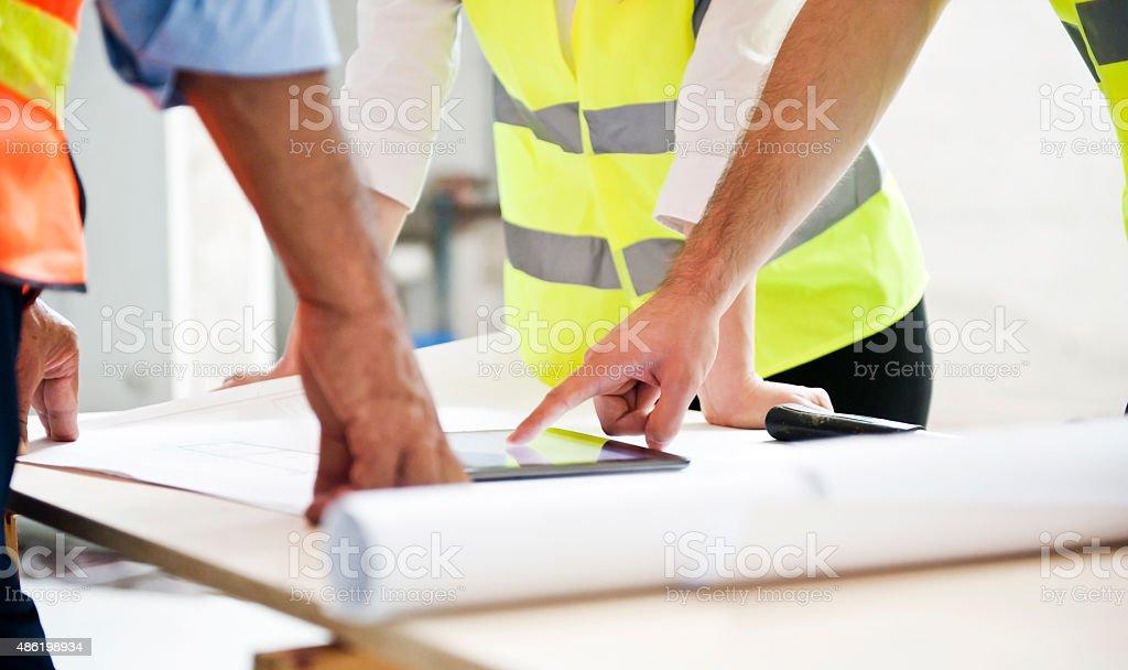 Engineers Examining Blueprint At Desk stock photo
