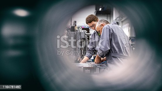Photo of engineers fixing a machine shot through a pipe. Focus on background.