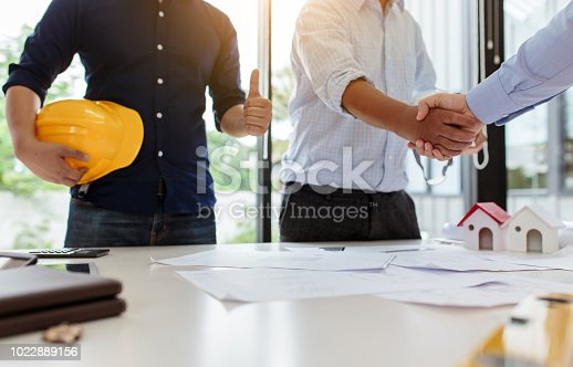 1055059750istockphoto Engineers handshake at meeting. Congratulations and agreed to do the project together 1022889156