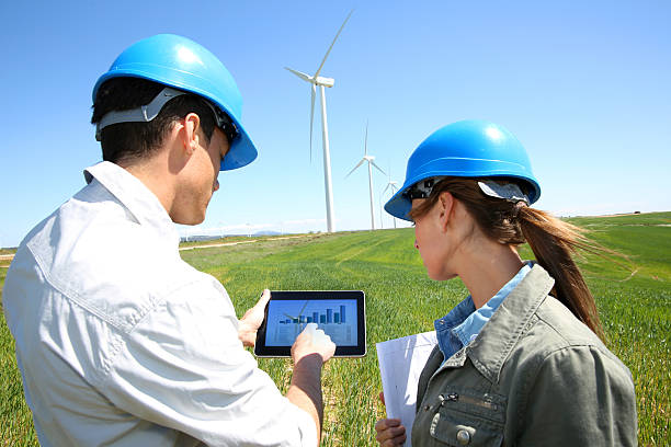 Engineers in front of  wind turbine using with tablet stock photo
