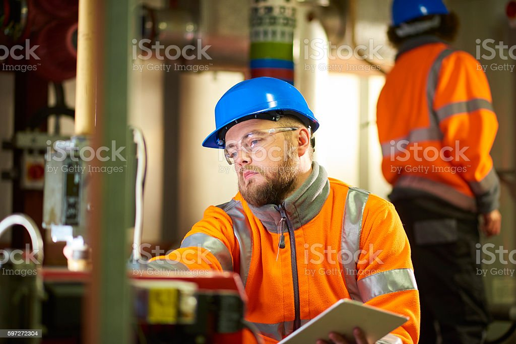 Engineer's inspecting boiler room machinery stock photo