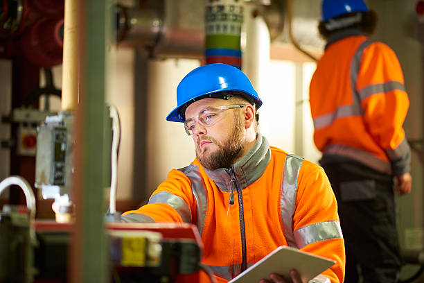 Engineer's inspecting boiler room machinery stock photo