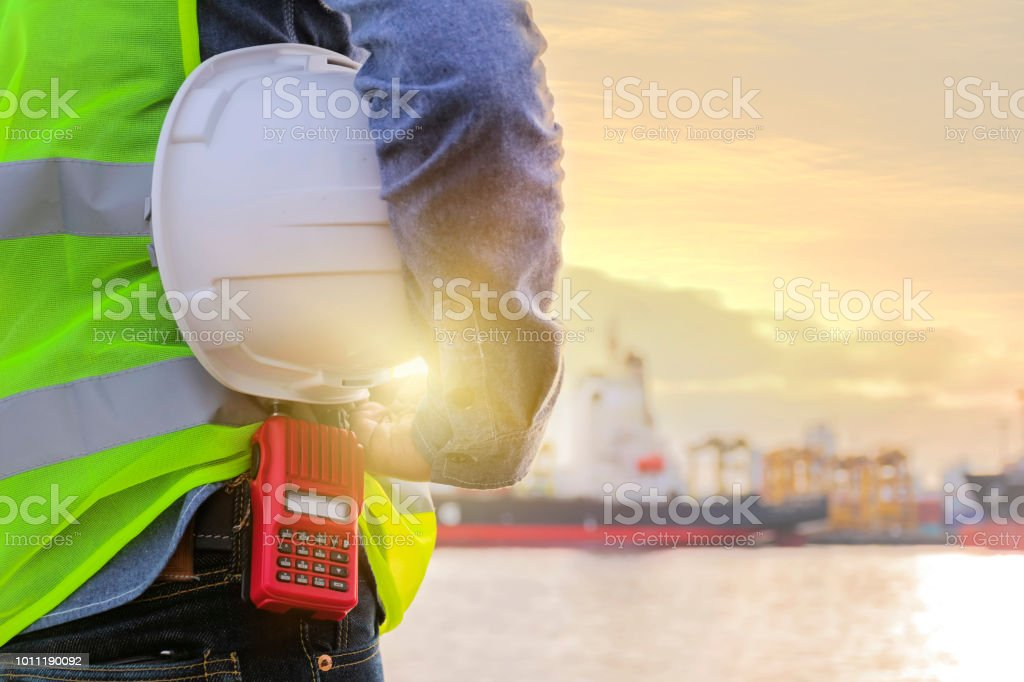 Engineers is listening to radio, Holding a white helmet. Working on...