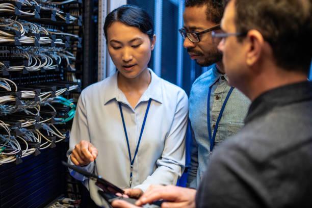IT-Ingenieure, die mit einem digitalen Tablet neben einem Server suchen – Foto