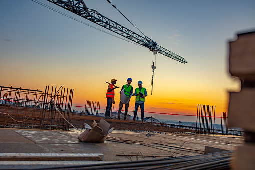 Photo of project manager visiting construction site with Multi-Ethnic construction workers standing on roof top at sunset. Business, building, industry, technology and people concept - smiling builder in hardhat with blueprint over group of builders at construction site under the tower crane.