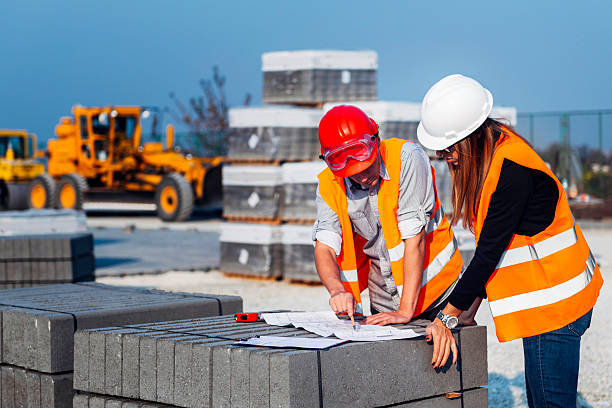 engineers looking at plans at construction site - civil engineer stock photos and pictures