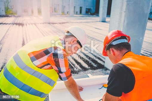 istock Engineers looking at plans at construction site 862318196