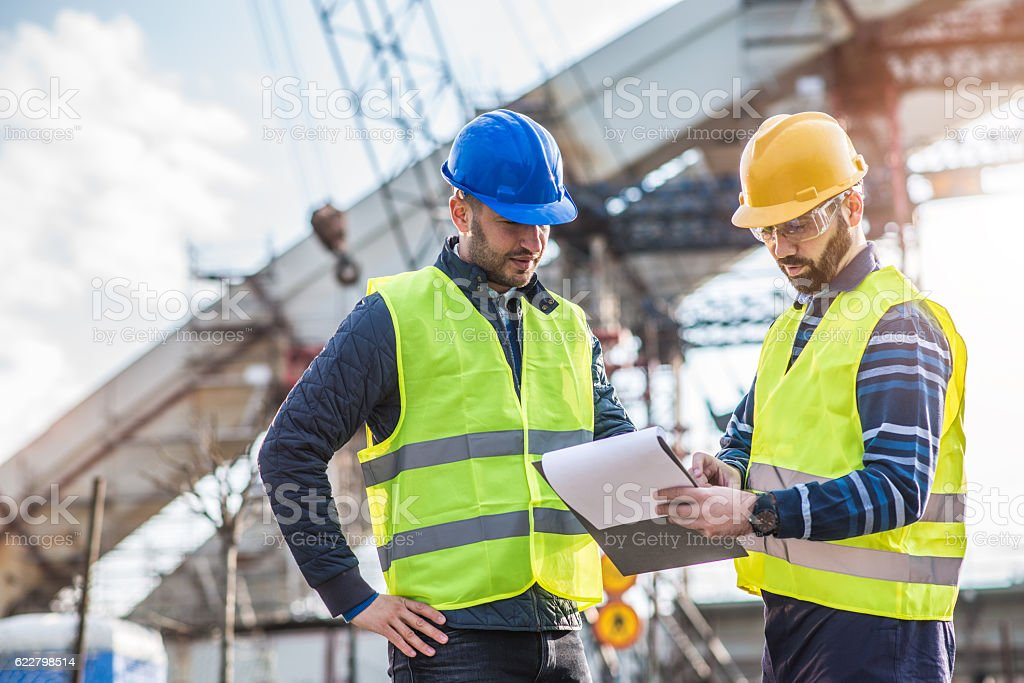 Engineers looking at project documents and discussing building process – Foto