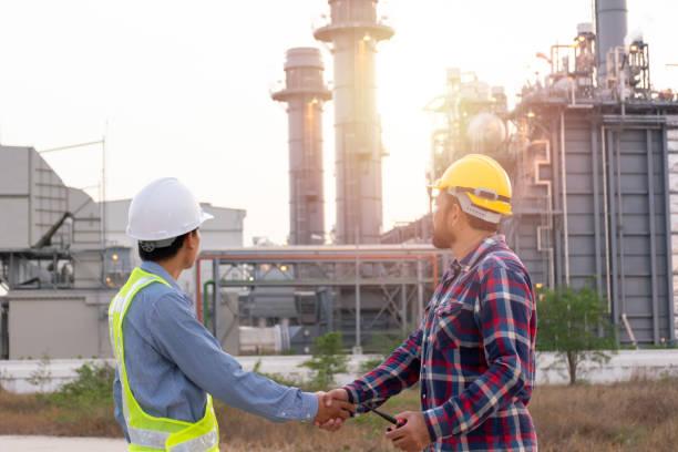 Los ingenieros hombres dan la mano a la central eléctrica. Área de energía de la zona Sunset intervalo de tiempo. Concepto de éxito, acuerdo y trabajo en equipo - foto de stock