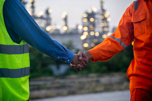 Engineers male shake hands at power plant. Energy power station area Sunset time interval. Concept success, agreement and teamwork stock photo