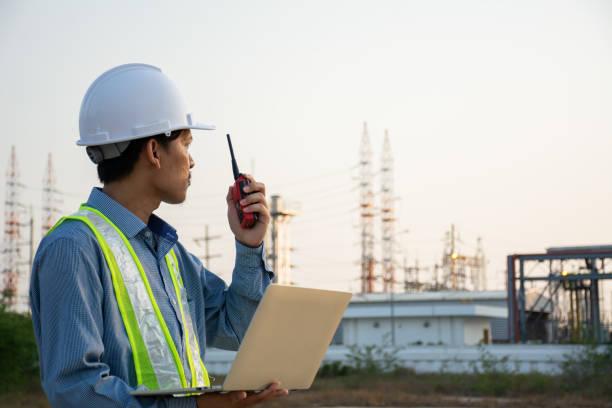 Ingenieros masculinos trabajando con el ordenador portátil y operan la radio para el control de seguridad de los trabajadores en la planta eléctrica. Zona de energía energética con cielo, puesta de sol. Seguridad conceptual, industria - foto de stock
