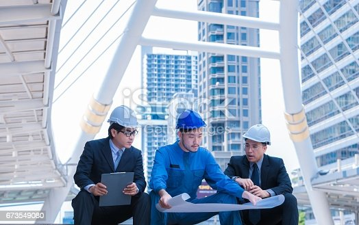 521012560istockphoto engineers meeting at terrace on top of construction site. Coworkers discussing. Boss and worker argue. Conversation in team.wear helmet hold paper plans 673549080