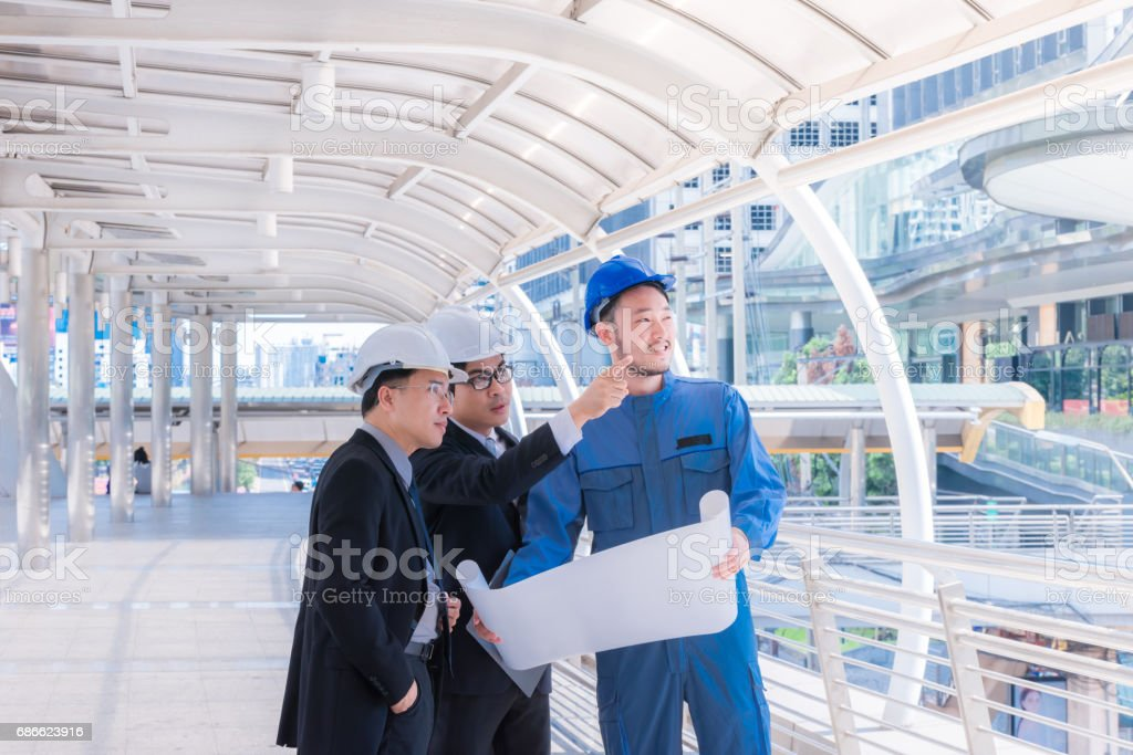 engineers meeting at terrace on top of construction site. Coworkers discussing. Boss and worker argue. Conversation in team.wear helmet hold paper plans stock photo