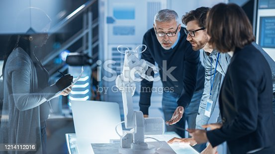 istock Engineers Meeting in Robotic Research Laboratory: Engineers, Scientists and Developers Gathered Around Illuminated Conference Table, Talking, Using Tablet and Analysing Design of Industrial Robot Arm 1214112016
