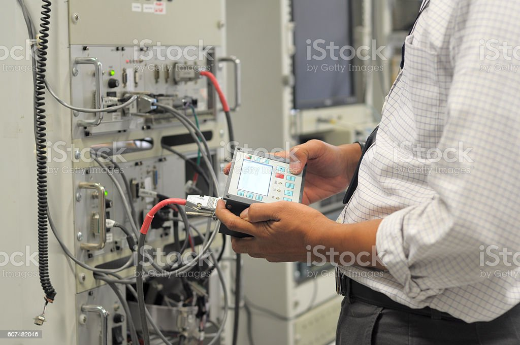 Engineers monitor electronic equipment used in communications systems.