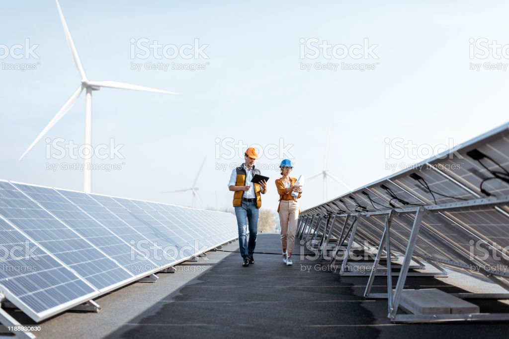 Engineers on a solar power plant View on the rooftop solar power plant with two engineers walking and examining photovoltaic panels. Concept of alternative energy and its service Adult Stock Photo