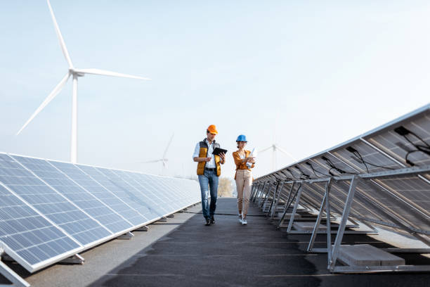Engineers on a solar power plant View on the rooftop solar power plant with two engineers walking and examining photovoltaic panels. Concept of alternative energy and its service engineer stock pictures, royalty-free photos & images