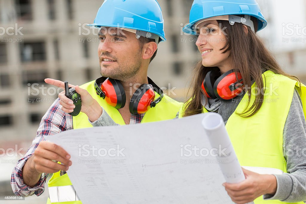Engineers on building site cheking plans stock photo