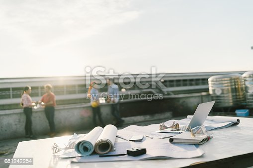 681242254 istock photo Engineers or architects relaxing after work at construction site. Focus on building's blueprints, laptop computer, and civil engineering tools. Industry projects or teamwork concept 681242254