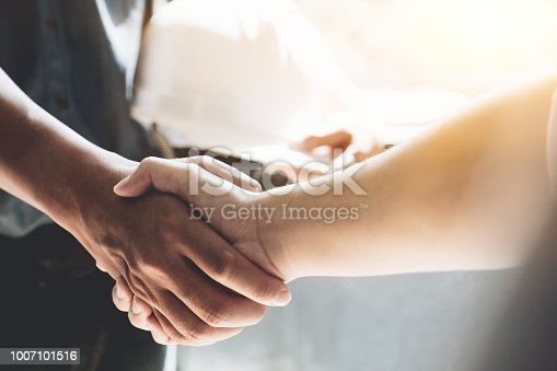 976560476 istock photo Engineers or architecture shaking hands at construction site for architectural project, holding safety helmet on their hands. 1007101516