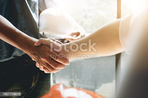976560476 istock photo Engineers or architecture shaking hands at construction site for architectural project, holding safety helmet on their hands. 1007726010