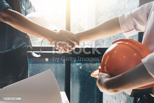 976560476 istock photo Engineers or architecture shaking hands at construction site for architectural project, holding safety helmet on their hands. 1009292368