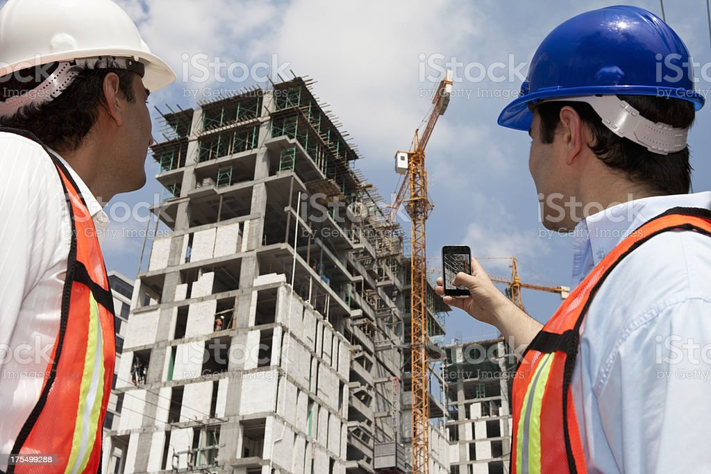 Engineers photographing a crane and building royalty-free stock photo