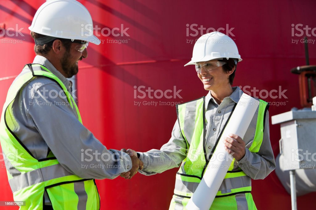 Engineers shaking hands by industrial water tower royalty-free stock photo