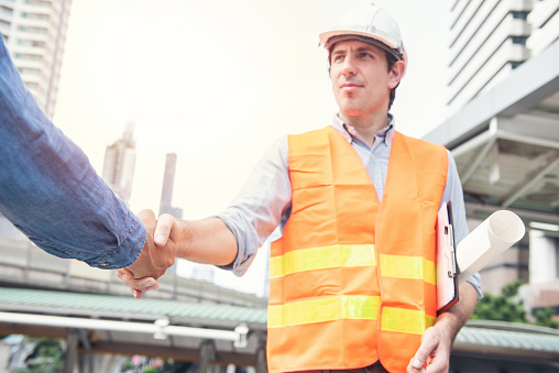 912867216 istock photo Engineers shaking hands with customer at construction site 1206237658