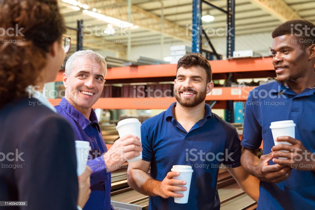 Engineers taking coffee break with female manager Engineers taking coffee break with manager in warehouse. Inspector is on visit in manufacturing industry. They are holding disposable cups. 20-24 Years Stock Photo