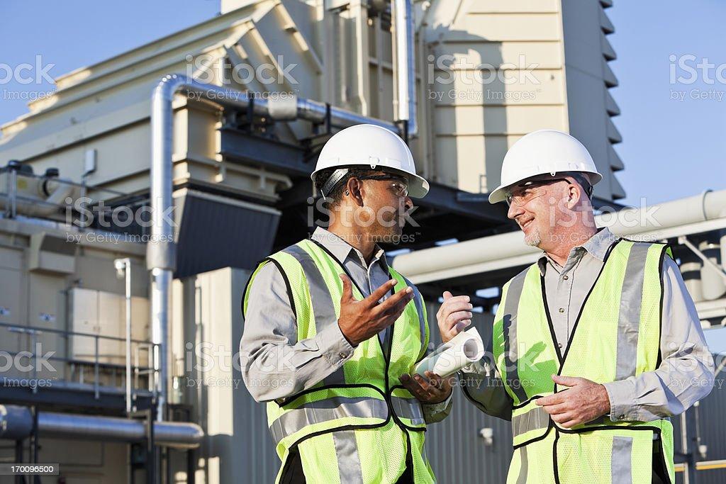 Engineers talking near power generator stock photo