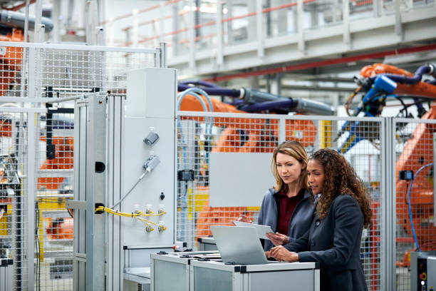 Engineers using technologies in auto industry Female engineers using technologies in automobile industry. Colleagues are discussing while standing in car plant. Confident professionals are working together. manufacturing stock pictures, royalty-free photos & images